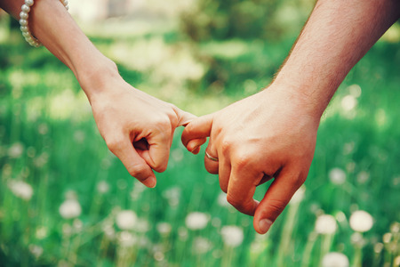 Photo for Married young loving couple holding hands each other in summer park, view of hands - Royalty Free Image