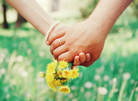 Young loving couple holding hands each other with bouquet of yellow dandelions in summer park, view of hands