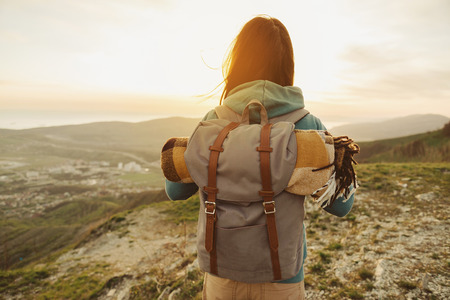 Foto de Hiker woman with backpack and sleeping bag walking in the mountains in summer at sunset - Imagen libre de derechos