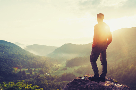 Photo pour Traveler young man standing in the summer mountains at sunset and enjoying view of nature. Image with color - image libre de droit