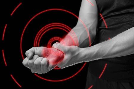 Foto de Pain in a male wrist. Man holds his hand, monochrome image, pain area of red color - Imagen libre de derechos