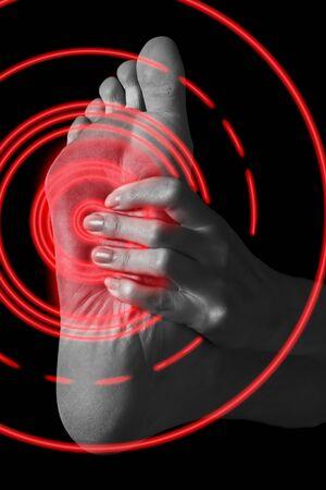 Foto de Pain in the female foot, monochrome image, pain area of red color - Imagen libre de derechos