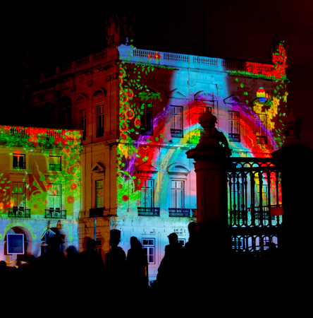 Photo pour Video Mapping in a building wall with silhouetted people watching. - image libre de droit