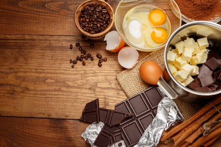 Foto de Baking chocolate cake in rural or rustic kitchen. Dough recipe ingredients on vintage wooden table - Imagen libre de derechos