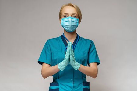 Photo for medical doctor nurse woman wearing protective mask and latex gloves - praying nad hoping gesture - Royalty Free Image