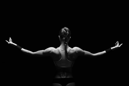 Foto de Athletic young woman showing muscles of the back and hands on a isolated black background - Imagen libre de derechos