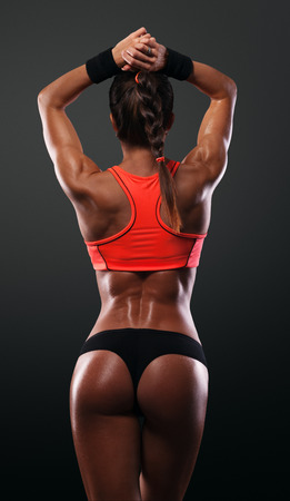 Photo for Athletic young woman showing muscles of the back and hands on a isolated black background - Royalty Free Image