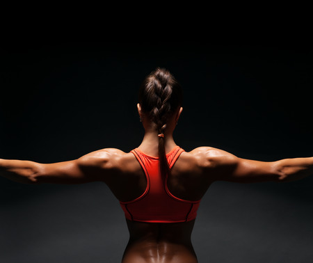 Photo pour Athletic young woman showing muscles of the back and hands on a black background - image libre de droit