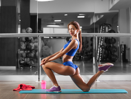 Foto de Attractive young woman is doing plank exercise while working out in gym - Imagen libre de derechos