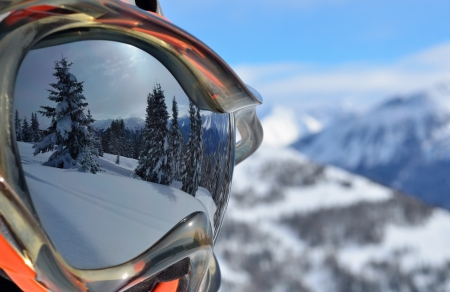 Photo pour Reflection of the winter mountain landscape in a ski mask - image libre de droit