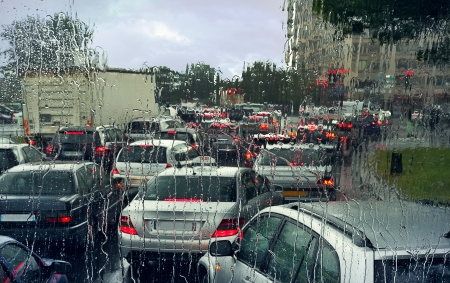View through wet windshield on cars in a traffic jam on rainy day in Paris, France
