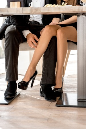 Photo for Young couple flirting with legs at the restaurant under the table - Royalty Free Image