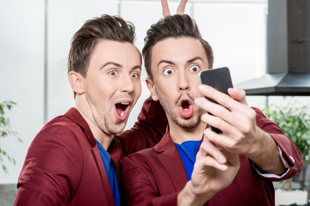 Foto de Friendly brothers twins having fun taking selfie photo with smart phone in the white home or restaurant interior - Imagen libre de derechos