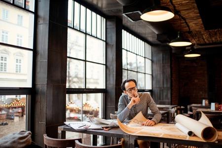 Foto de Creative architect thinking on the big drawings in the dark loft office or cafe. General plan with windows - Imagen libre de derechos