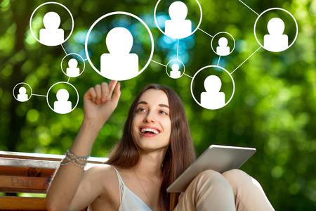 Foto für Young woman adding friends in social media with digital tablet in the park - Lizenzfreies Bild