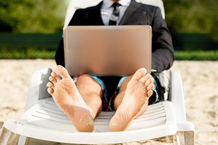 Foto de Businessman dressed in suit and shorts working with laptop on the sunbed at the beach - Imagen libre de derechos