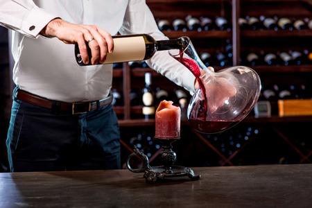 Foto de Sommelier pouring wine to the decanter in the wine cellar - Imagen libre de derechos
