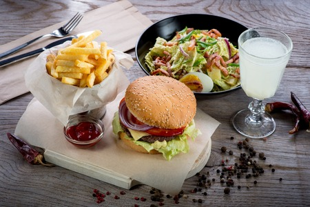 Photo pour American lunch with hamburger, fries, salad and lemonade on wooden table - image libre de droit