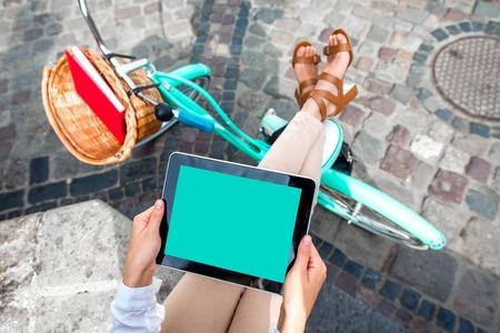 Foto de Holding tablet in the hands with bicycle on background in the city - Imagen libre de derechos