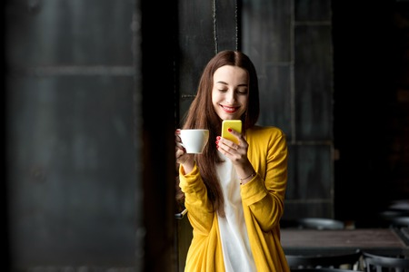 Photo pour Young and pretty woman in yellow sweater using phone holding a cup of coffee in the dark cafe interior - image libre de droit