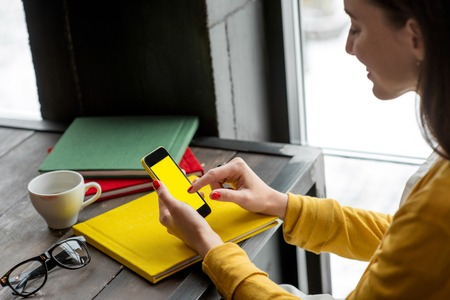 Photo pour Woman using smart phone on the table with colorful books in the cafe near the window.  - image libre de droit