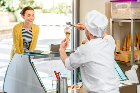 Photo pour Confectioner selling ice cream to young woman in the pastry shop - image libre de droit