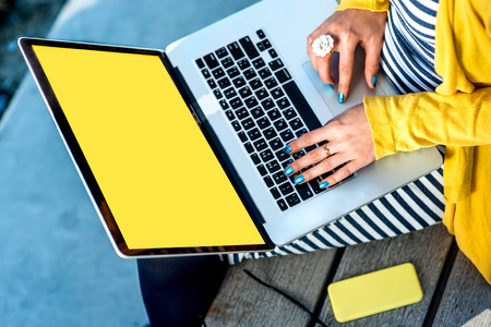 Photo pour Woman typing on laptop with empty yellow screen sitting on the bench - image libre de droit
