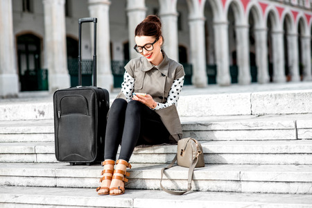 Photo pour Young woman dressed in coat and glasses with travel bag using phone on the stairs at Republic square in Split city - image libre de droit