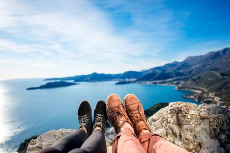 Foto de Couples legs in shoes together on the mountains and sea background - Imagen libre de derechos