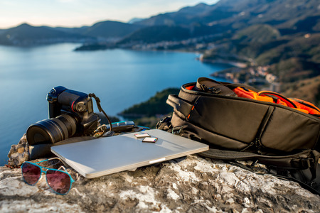 Foto de Travel photographer equipment on rocky mountain with beautiful landscape on the background - Imagen libre de derechos
