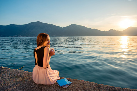Photo for Young woman sitting with coffee cup on the pier at sunrise with beautiful mountains and sea on background - Royalty Free Image