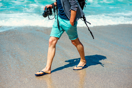 Photo for Man in shorts walking with photo camera on the beach - Royalty Free Image