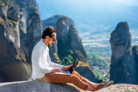 Photo for Well-dressed man working with laptop sitting on the rocky mountain on beautiful scenic clif background near Meteora monasteries in Greece. - Royalty Free Image