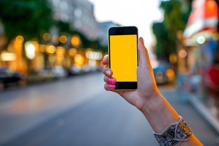 Foto de Woman hands using mobile smart phone with empty screen on street evening light with colorful bokeh background - Imagen libre de derechos