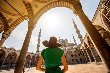 Foto de Young woman traveler in black hat and green dress looking on amazing Blue Mosque in Istanbul, Turkey - Imagen libre de derechos