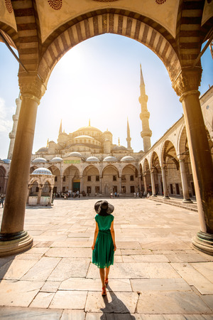 Photo pour Young woman traveler in the green dress and hat walking to the Blue Mosque in Istanbul - image libre de droit