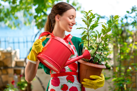 Photo for Young woman in apron and working gloves taking care for  flower in in the garden - Royalty Free Image