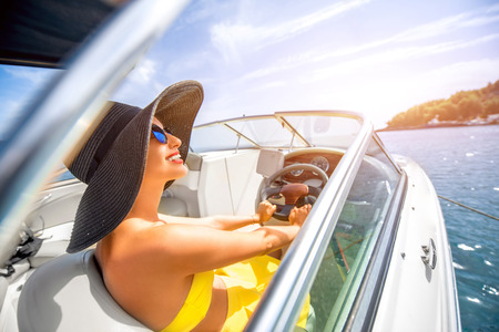 Photo pour Young and pretty woman in yellow skirt and swimsuit with hat and sunglasses driving luxury yacht in the sea. - image libre de droit