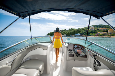 Foto de Young and pretty woman in yellow swimsuit standing on the yacht floating in the sea with view on the island - Imagen libre de derechos