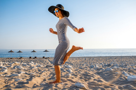 Foto de Young and elegant woman in stripped dress with a hat jumping on the beach on sunset - Imagen libre de derechos