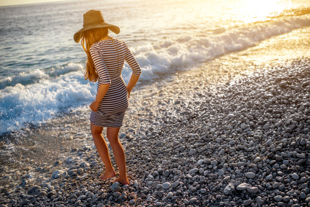 Foto de Young and elegant woman in stripped dress with a hat walking to the sea on the beach on sunset - Imagen libre de derechos