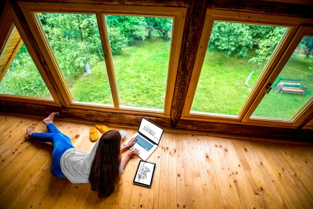 Foto de Woman in jeans and white shirt lying on the floor with laptop and tablet near the window with garden view in cozy wooden cottage. - Imagen libre de derechos