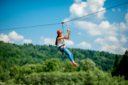 Photo pour Young woman in casual wearing with red helmet riding on a zip line in the mountains. Active kind of recreation - image libre de droit
