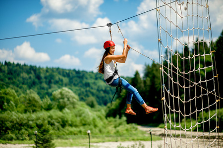 Foto de Young woman in casual wearing with red helmet riding on a zip line in the mountains. Active kind of recreation - Imagen libre de derechos