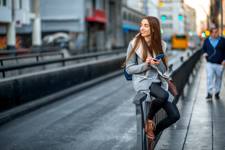 Foto de Young woman in casual gray clothes using smartphone sitting near the street on the gray city background - Imagen libre de derechos