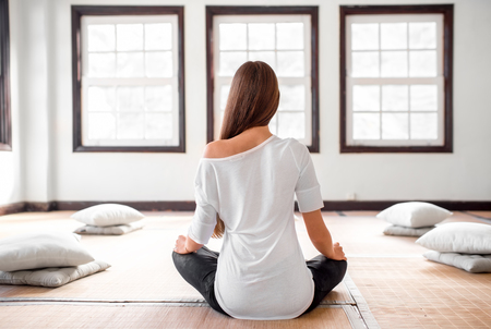 Photo pour Young and positive woman in white t-shirt and black leggings practicing yoga in the bright interior with big windows. - image libre de droit