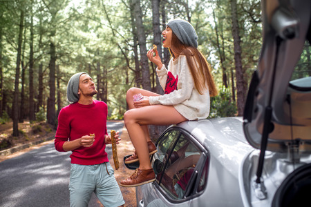 Foto de Young and lovely couple in sweaters and hats having fun, eating baguette with jam near the car on the roadside in the pine forest. Young family having quick snack while traveling - Imagen libre de derechos