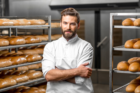 Foto de Portrait of handsome baker at the bakery with breads and oven on the background - Imagen libre de derechos