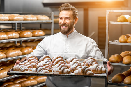 Photo pour Handsome baker in uniform holding tray full of freshly baked croissants at the manufacturing - image libre de droit