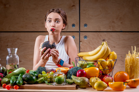Photo for Hungry woman eating black burger at the table full of fruits and vegetables on the wooden background. Choosing between healthy and unhealthy food - Royalty Free Image